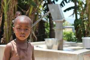Haitian Boy By Hand Pump