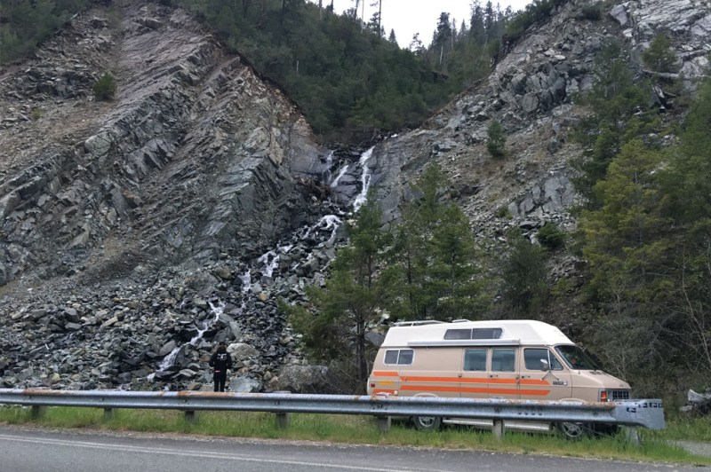 camper van parked beside waterfall while camping on the smith river, california