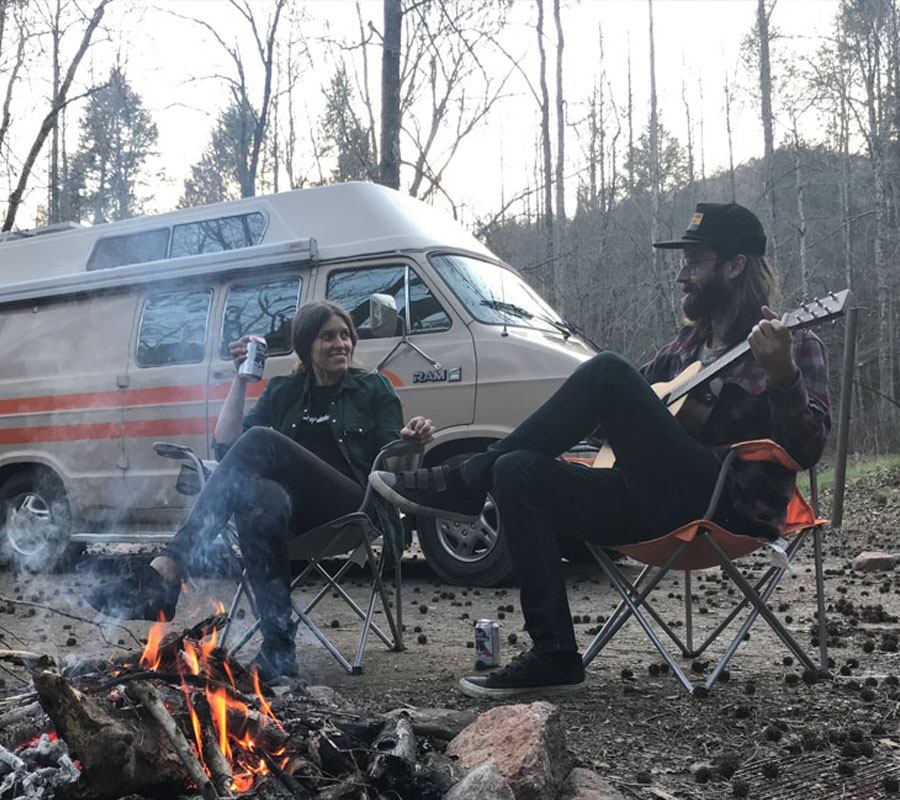 Couple sitting by the campfire with a guitar and beers