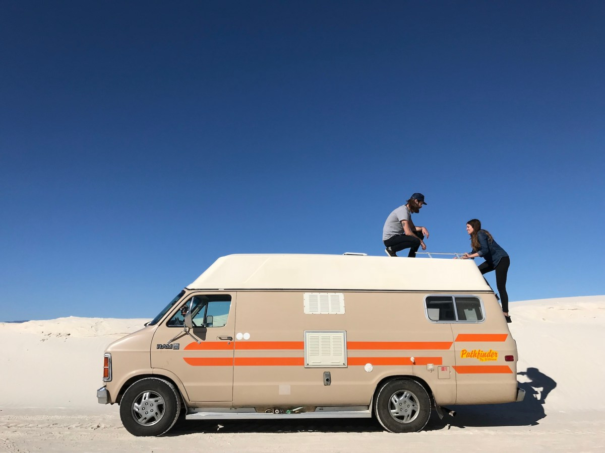 Man standing on roof of camper van while woman climbs down ladder at White Sands National Monument