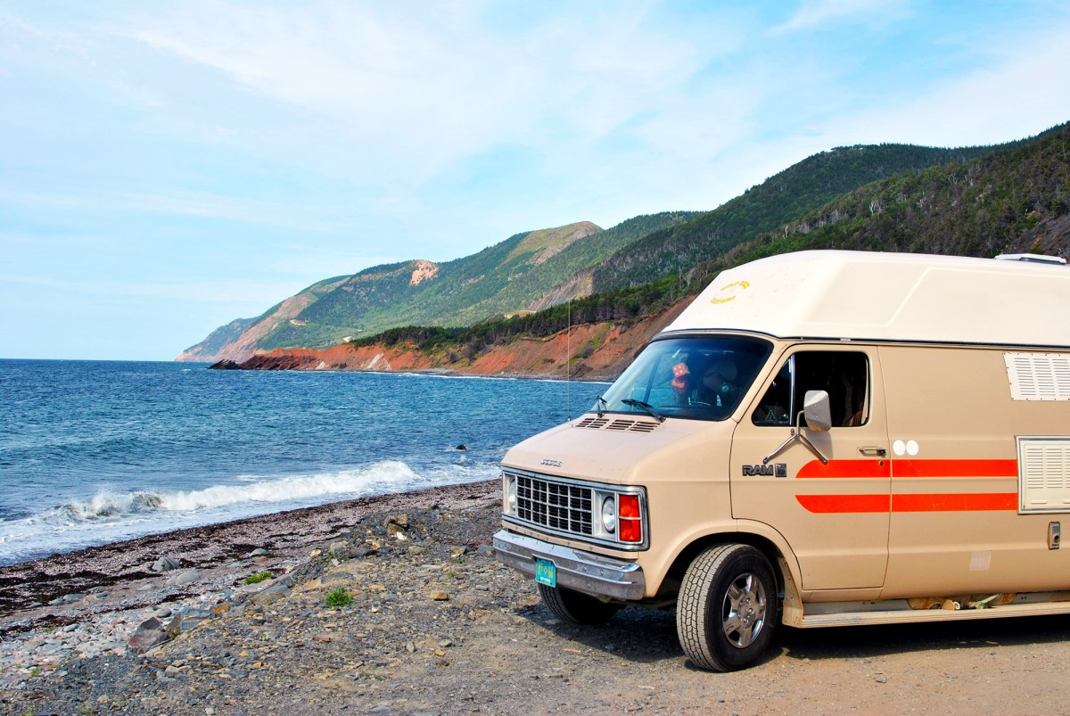 Camper van parked on the beach with rugged mountains