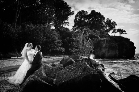 A black and white image of a bride standing and leaning into the groom's arms as he sits backs and rest on a large boulder on Catawba Island with large trees behind them and the shoreline of Lake Erie to their left.