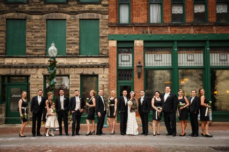 An image of a bride wearing her gown and a fur jacket posing with her groom in a black tuxedo along with their wedding party all in black with gold accents outside the landmark Bender's Tavern, a brick and stone building with dark green accents, on a December day in Canton, OH