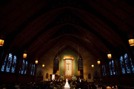 An image of a bride and groom standing facing the altar at the Fairmount Presbyterian Church where the chapel is darkened and the evening light is glowing blue through the stained glass windows and the altar is glowing with golden light where the ornate gold cross in the background is set up in front of a green wall.