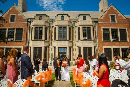 An image of a bride being escorted by her dad down the stone aisle with the brick and stone building of the Hathaway Brown School in the background holding her orange bouquet while the guests stand up watching from white folding chairs lined with large orange bows made from tulle.