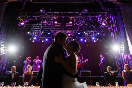 An image of a bride and groom slow dancing on the floor of the House of Blues in Cleveland with the head table in the background up against the stage where the band is playing under purple lights.