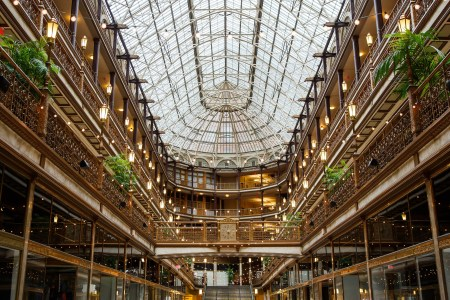 An image taken from the middle of Cleveland's oval shaped Arcade looking up from the ground floor towards the windowed ceiling and all of the levels of balconies with gold and wrought iron railings and cafe lighting draped around the room.