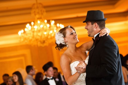 A waist high angled image of a bride in her white strapless gown with a feather in her hair smiling and dancing with the groom in his black tux with a formal hat inside a reception room glowing with a golden color at the McKinley Grand Hotel with a blurry chandelier in the background.