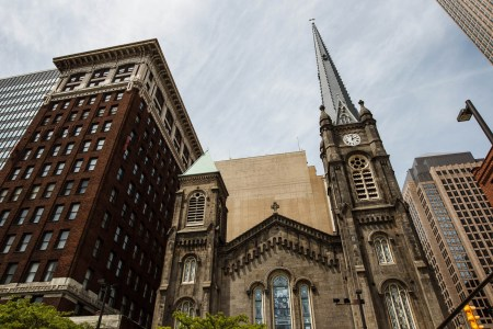 An outside picture of the front of the Old Stone Church in downtown Cleveland with the ornate stained glass windows and tall steeple nestled between other buildings under a blue and cloud streaked sky.