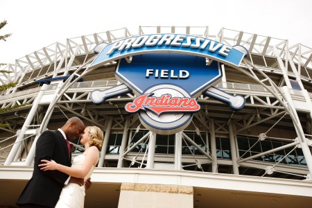 An image of a bride with her hair in an updo and white strapless dress embraces her groom in his dark tuxedo with foreheads touching in the left side of the photo standing directly in front of the Cleveland Indians stadium with the Progressive Field Indians sign in the upper middle of the photo.
