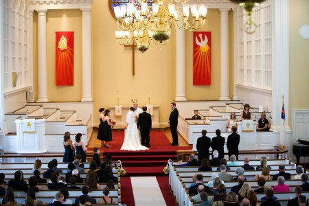 A bride and groom stand at the altar of a red carpeted church with yellow painted walls and white pillars along the back wall as well as white tiered pews on either side of the stage and red orange flags hanging from the walls as the wedding guests watch.