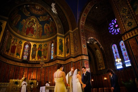 An image of a bride and groom facing each other holding hands in the lower right side of the photo with a priest and his raised hand praying over them inside the ornate sanctuary of St. James church decorated in dark browns, red, greens, and blues with some gold accents with paintings of saints on the arched and rounded walls and the left and purple colored stained glass windows on right.