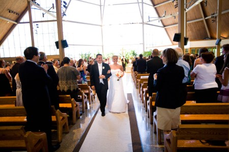 A bride and groom walking arm and arm back down the center aisle in the center of the photo with a wall of windows full of bright white light behind them and the wedding guests standing at the wooden pews on either side of the aisle at St. Paschal Baylon Parish.