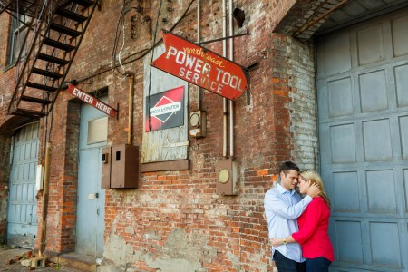 An image taken outside up against an industrial looking brick building of an engaged couple with their arms around each other and leaning with their foreheads pressed against each other in the lower right corner of the photo where the corner of a brick building meets a blue garage door and the upper left of the photo has red signs and a wrought iron escape stairs attached to the building.