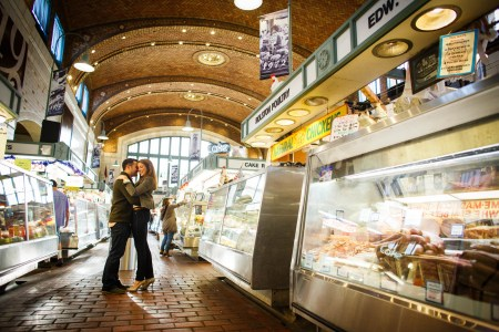 An engaged couple with jeans and olive green colored tops stand embracing with their heads together on a brick floor inside a bakery row of the Westside Market in Cleveland with an brick arched wall in the background with a wall of windows and bakery and food display cases on either side of the couple.