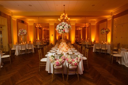 An image of a reception room at Brookside Country Club in Ohio is decorated with golden uplights where rectangular tables surround the outer walls and a large head table is set in the center of the room all with gold and white chairs and the bride and grooms chairs are placed at the head of the table decorated with arched pink and white flowers.