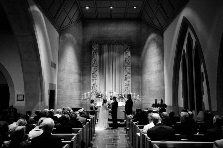 A black and white image of a bride and groom standing facing each other at the altar of St. Paul's Episcopal Church with the priest in the center facing the camera and the maid of honor to the left of the bride and the best man to the left of the groom with tall candelabras light on the altar with a tall two story stone wall behind them and guests seated in the wooden pews on either side of the aisle.