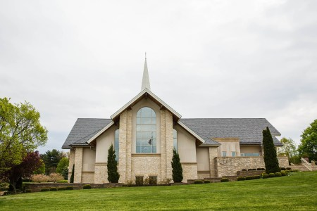 An outdoor shot of the sand colored stone chapel at Walsh University sitting on a bright grassy slope with a cross on top of a steeple under a grey sky.
