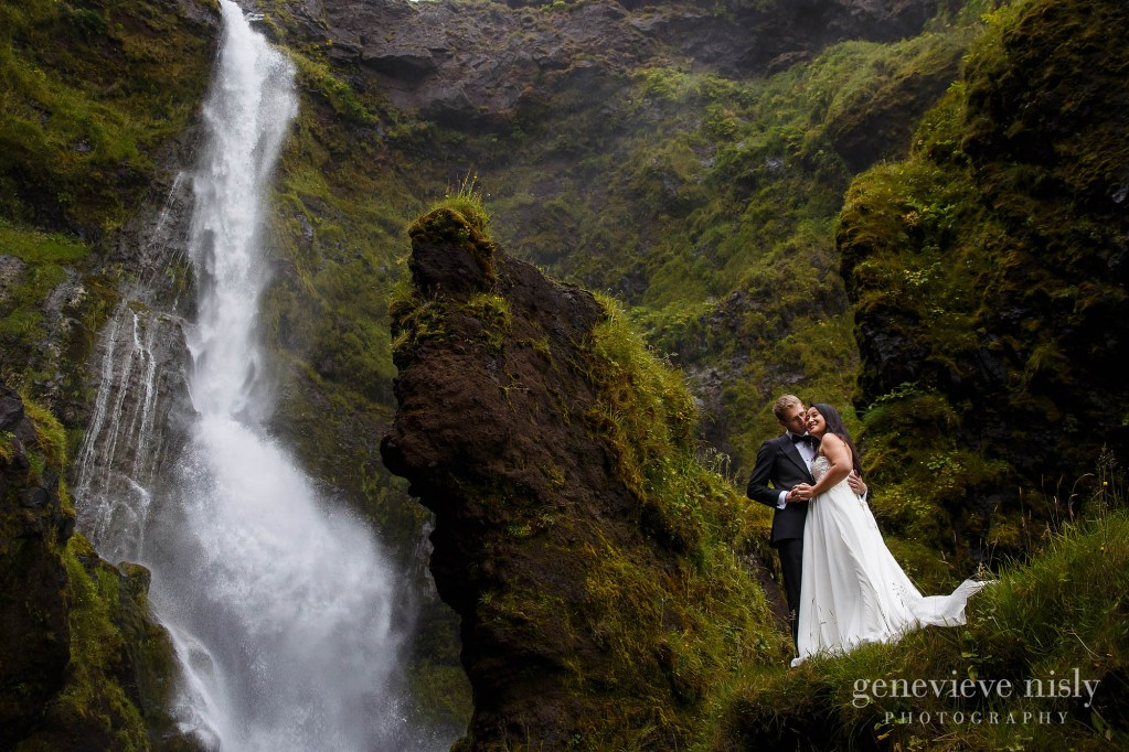 Bride and groom standing near a waterfall during their destination wedding in Iceland.