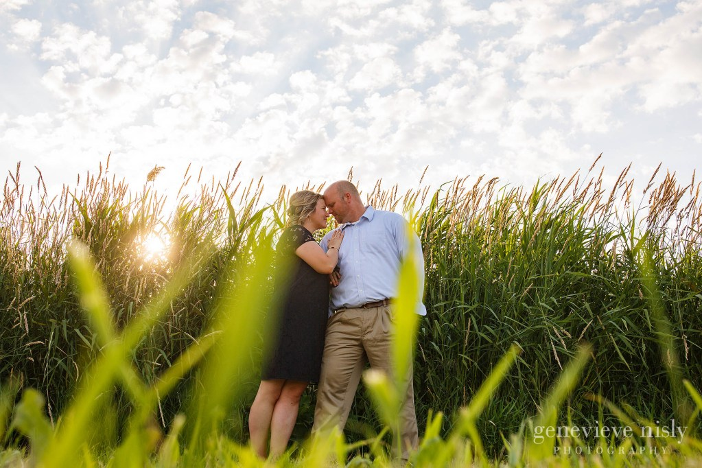 A huron engagement session with couple standing in front of tall grasses near the break wall.