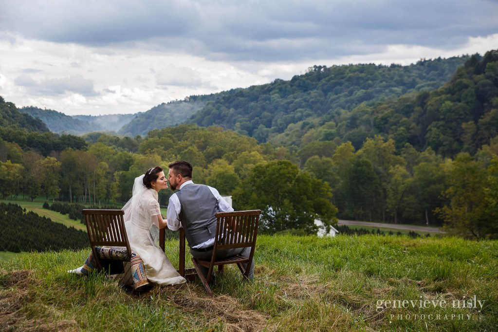 Bride and groom sit at a table overlooking a valley on their wedding at Running River Farm near mohican state park in Ohio.