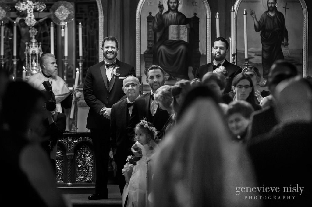 Groom watches his bride walk down he aisle towards him with her dad.