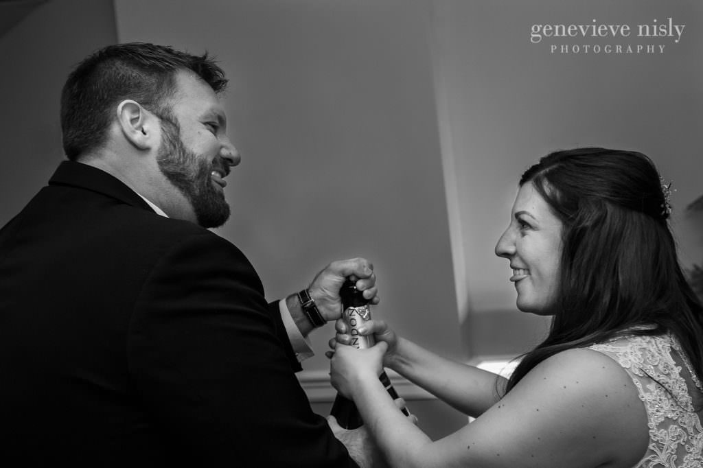 Bride and groom share a look while popping the cork out of a bottle of champaign.