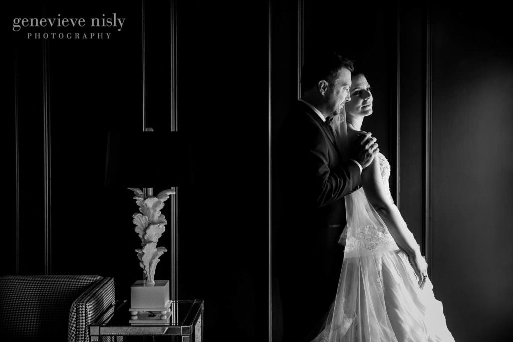 Window lit black and white of the bride and groom on their wedding day.