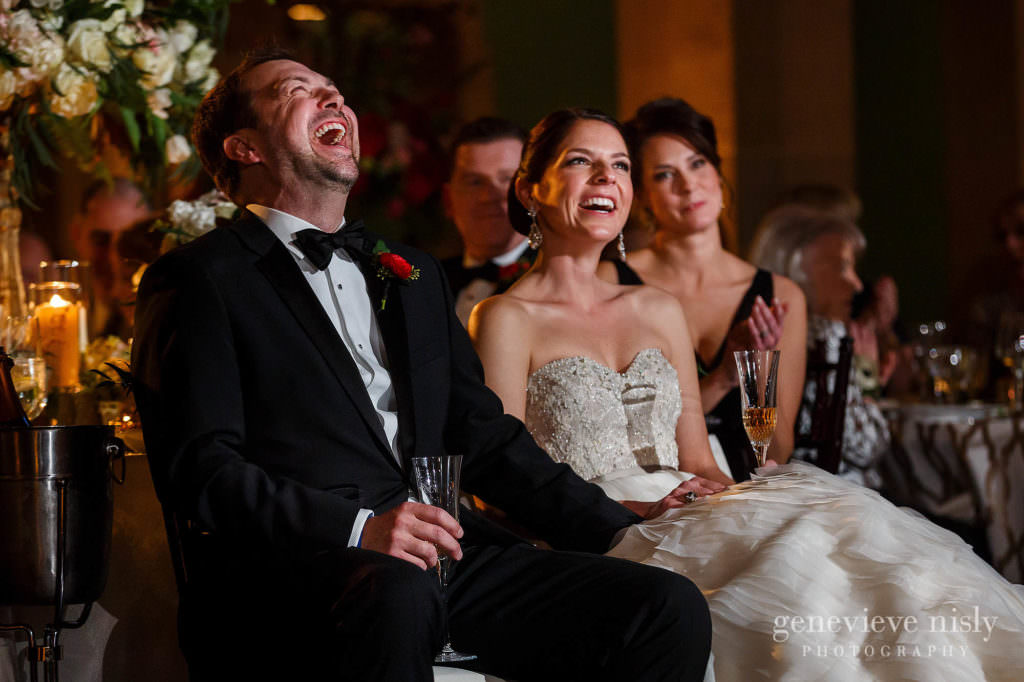 Bride and groom laugh during the best man's toast.