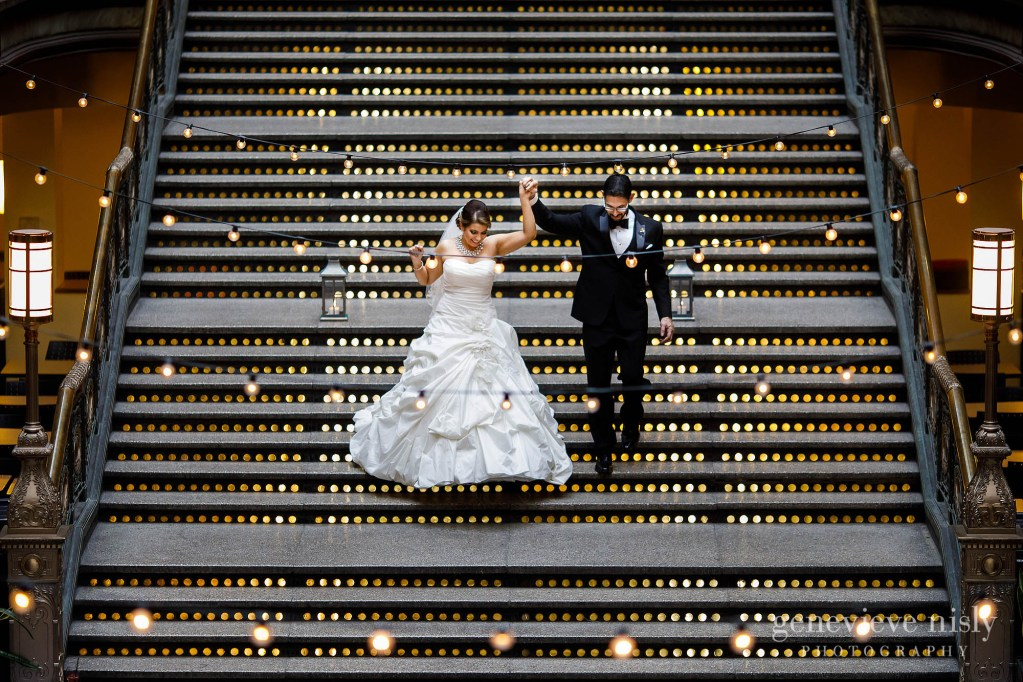 Cameron and Daniel walk down the grand staircase as they are introduced into the reception during Hyatt Arcade wedding in Cleveland, Ohio.
