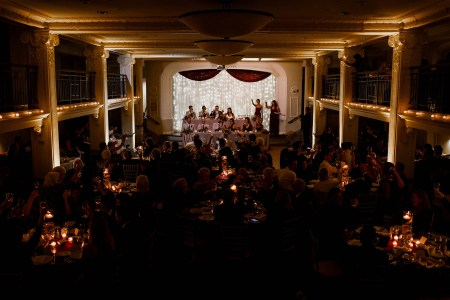 A picture of a wedding reception set in a the darkened ballroom at Park Lane where the guests are seated at round tables on the ballroom floor raising their glasses in a toast while the wedding party is at tiered rectangular tables with white twinkle lights under tulling behind them.