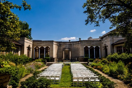 A photo of plain white folding chairs set in two sections with a middle empty aisle set up for a wedding ceremony in a patch of grass inside the stone walled Hanna Garden with thick green foliage bushes and plants lining the sides inside the Western Reserve Historical Society Museum.
