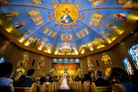A bride and groom stand facing the altar inside the ornate Holy Trinity Greek Orthodox Church in Ohio with a round domed ceiling painted with a blue background and angelic images and stained glass windows.