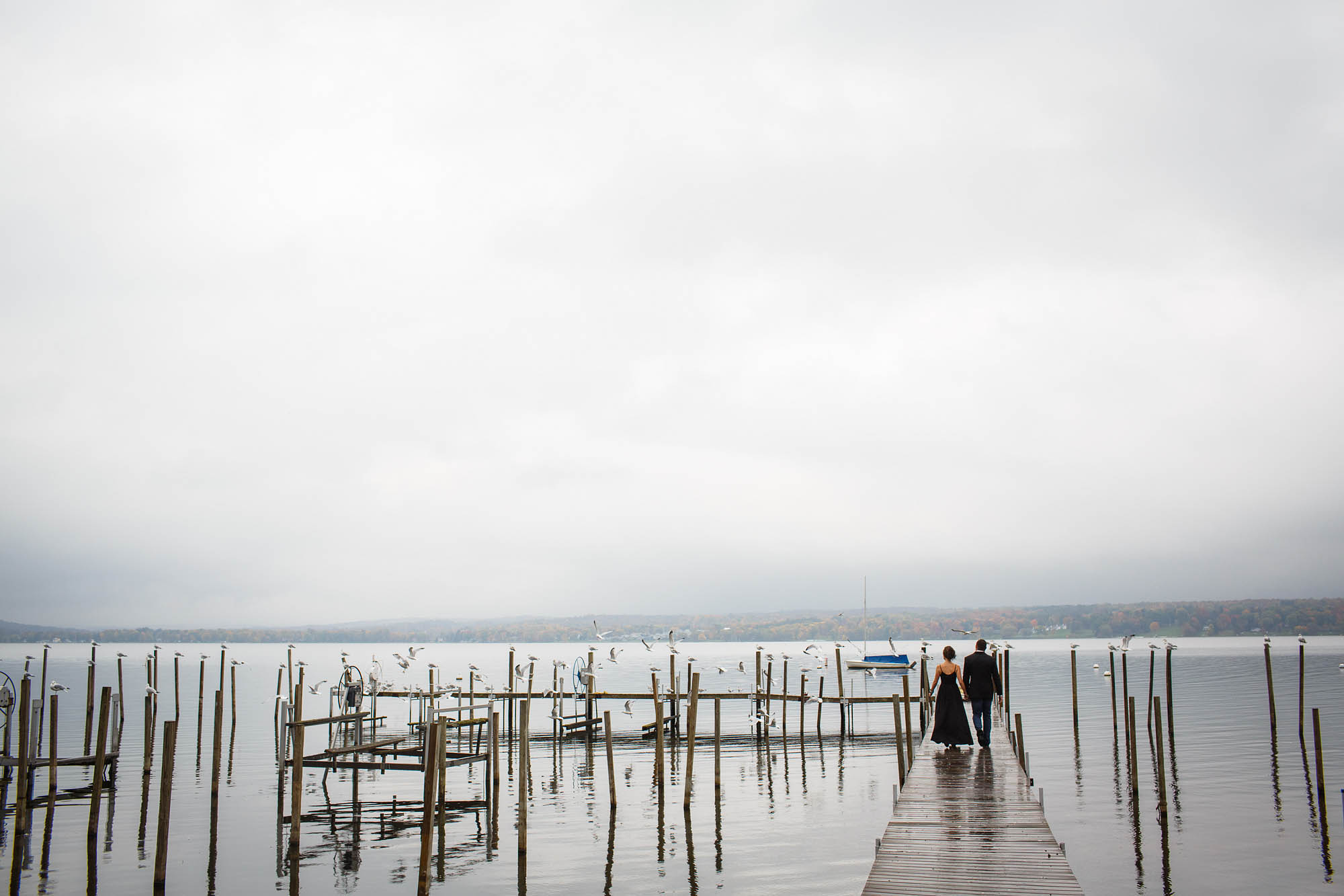 Couple walks out into the dock in the rain during their engagement photo session in Chautauqua, New York.