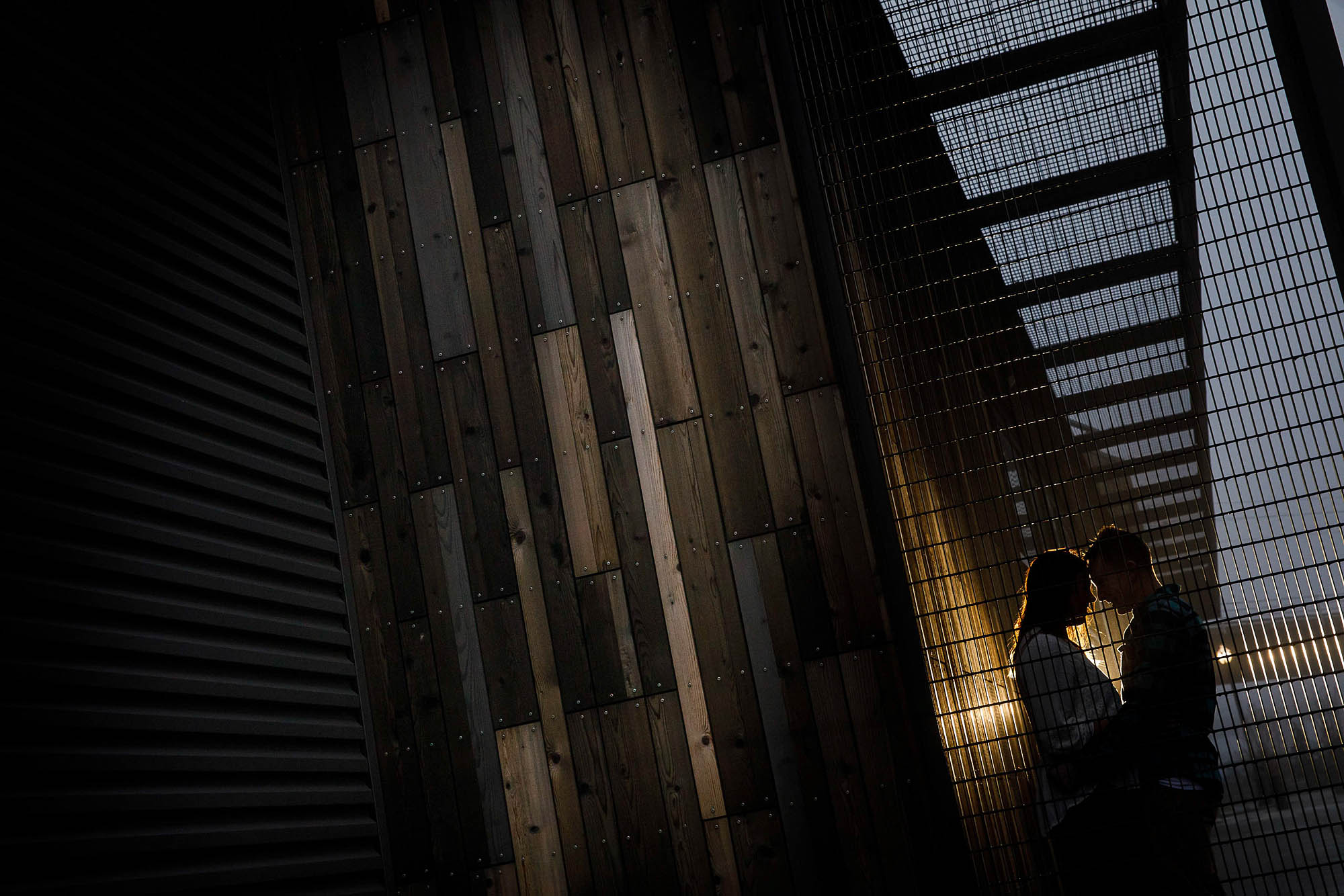 Couple by a wood slat wall at night.