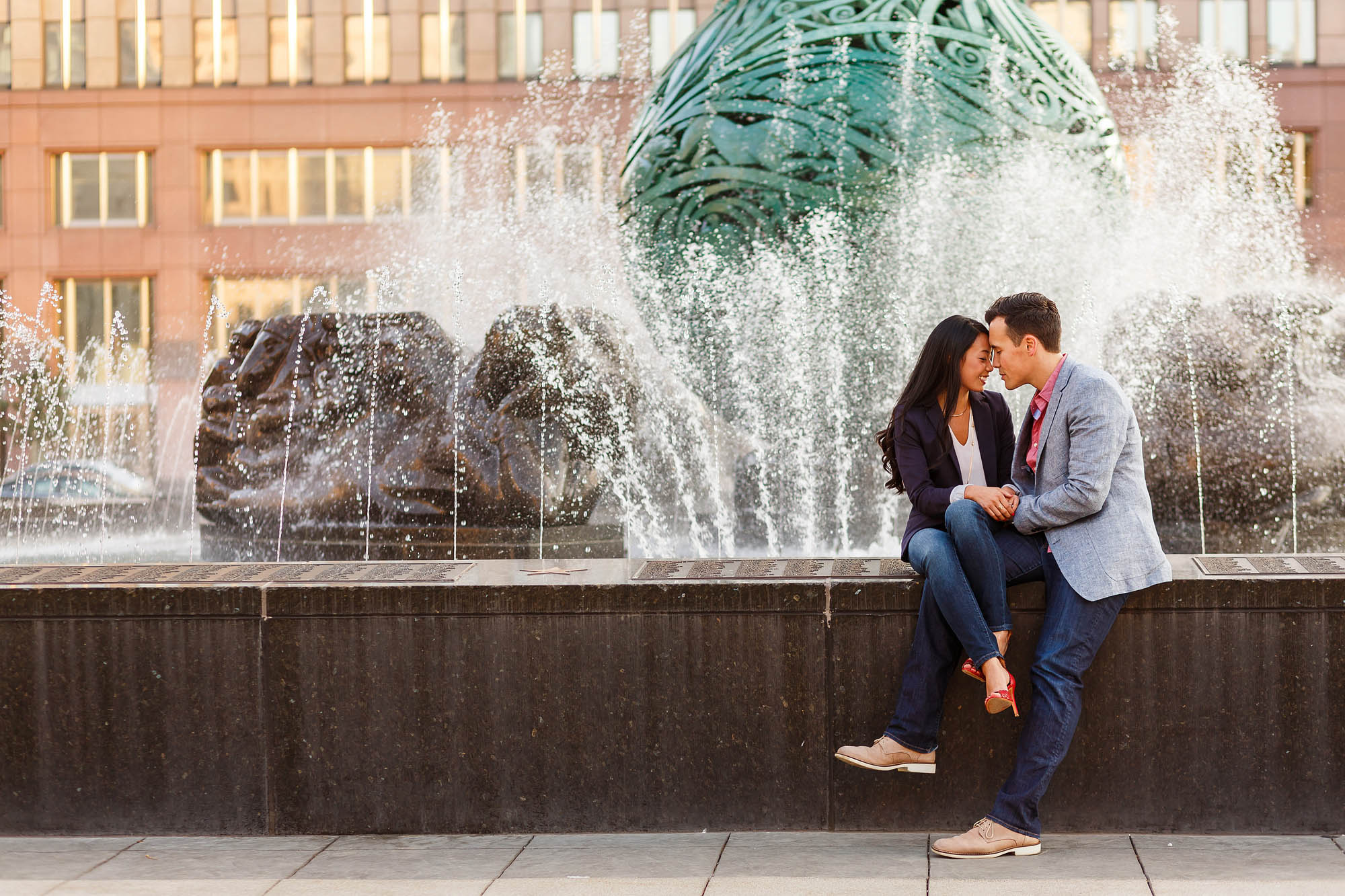 An engaged couple sit on the ledge of a fountain leaning in with foreheads touching while the fountain water sprays behind them with a red brick building in the background in Cleveland, Ohio.