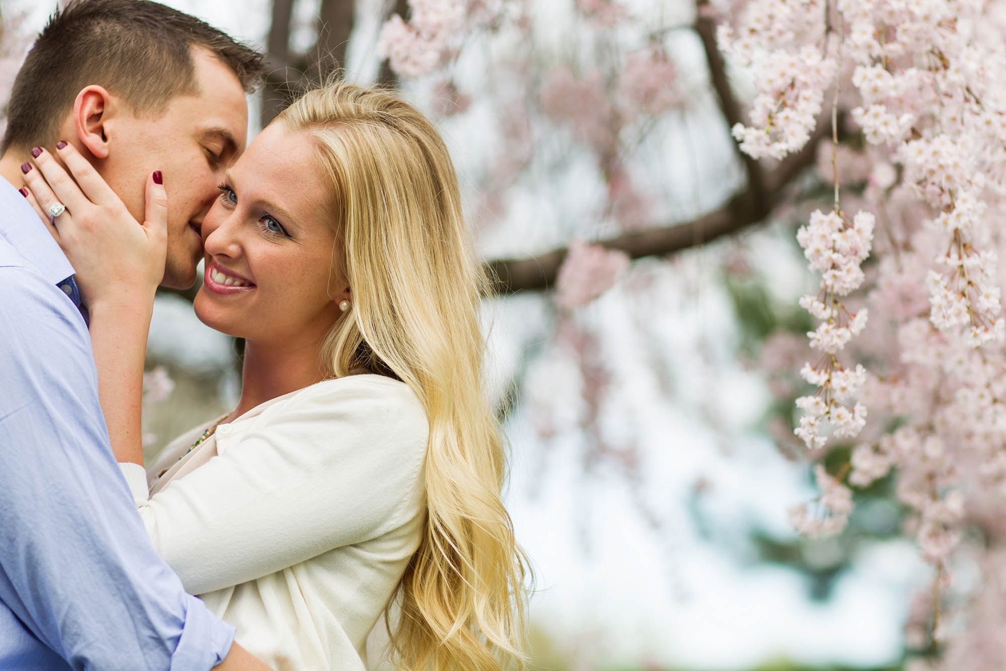 An engaged couple stand underneath a tree in spring that is flowering while the man leans into to kiss the woman's cheek on a bright day in Cleveland, Ohio.