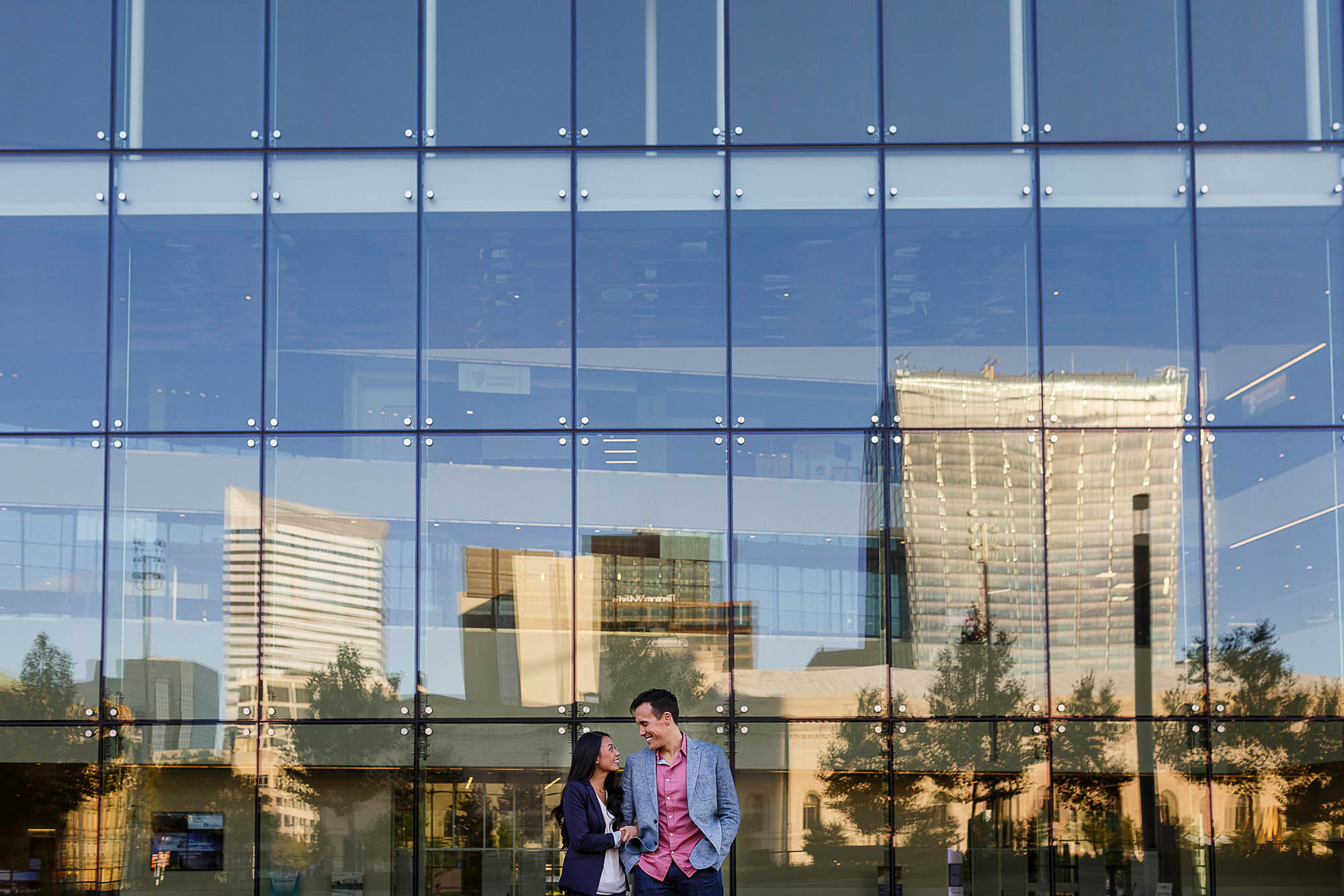 A picture of an engaged couple taken from a distance and waist up where the couple has their arms linked and heads turned toward each other while they stand up against a glass windowed building in downtown Cleveland with the skyline reflecting in the glass.
