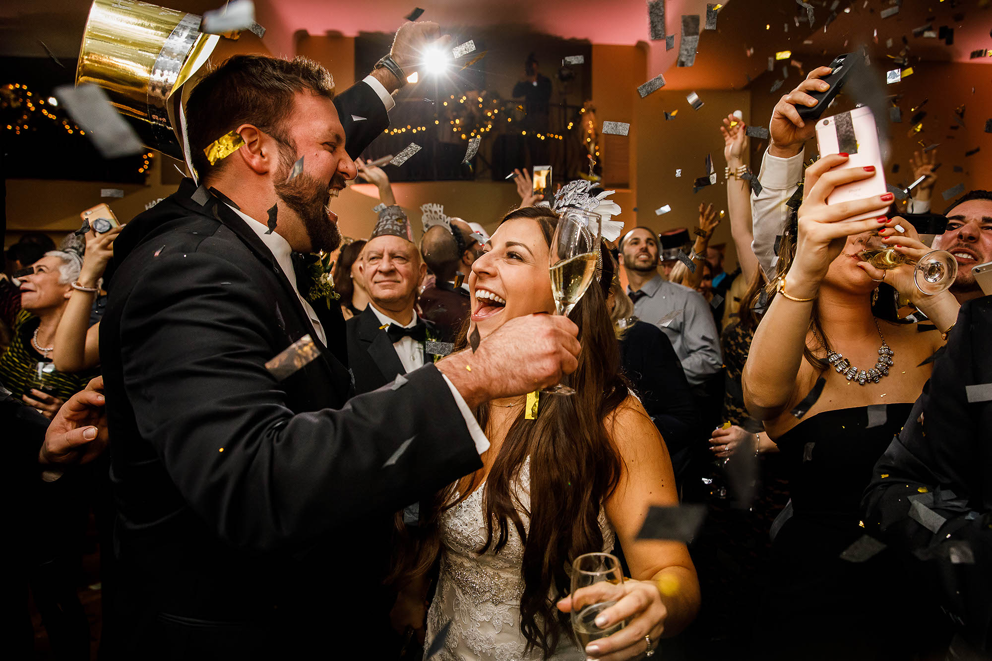 A happy bride and groom toast each other with champagne as confetti falls during their New Year's Eve wedding reception held at the Onesto Hotel located in downtown Canton, Ohio.