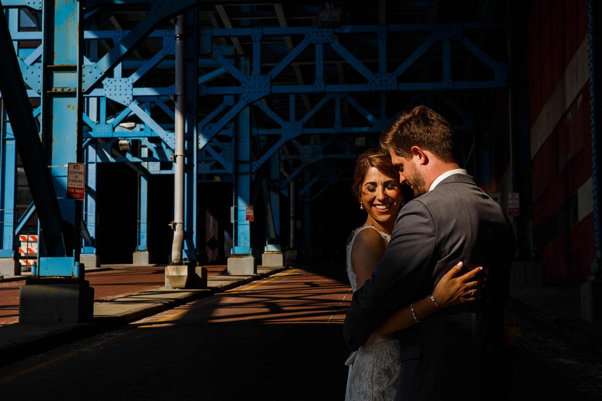 A bride and groom hug in the glow of the sun as they stand under one of the iconic blue steel bridges located in Downtown Cleveland, Ohio before heading off to their wedding reception.