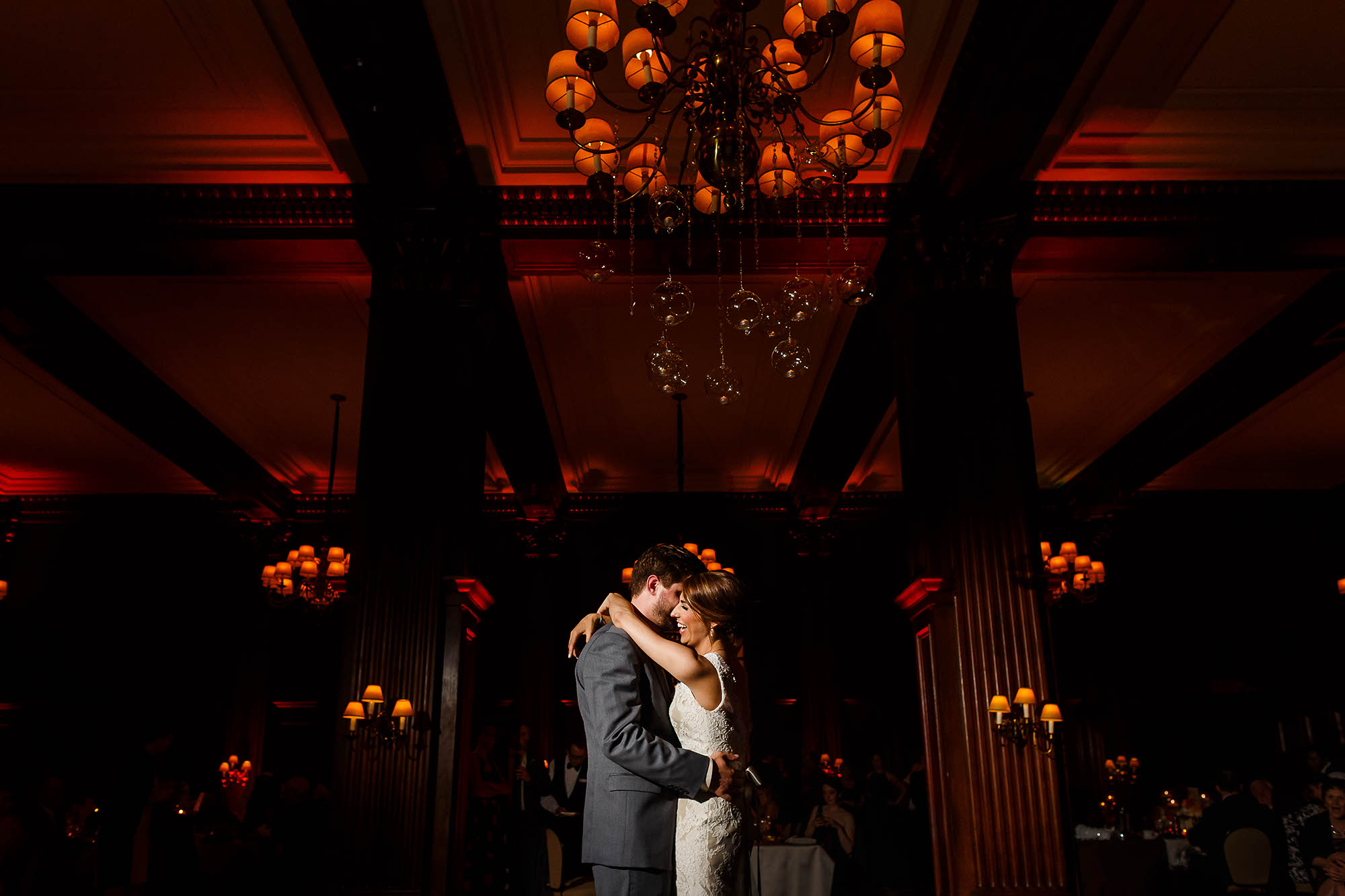 A bride and groom with their arms around each other during their first dance at the ceremony under a chandelier on the floor of the Union Club in Cleveland, Ohio.