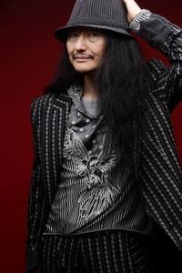 Foto do Shiro Sagisu. Um home asiático de cabelo longo e preto e bigode, veste uma camisa preta e um chapéu cinza.