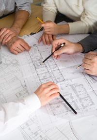 Commercial electricians reviewing location blueprints for building