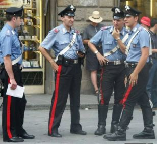 Four Italian policemen in light blue shirts