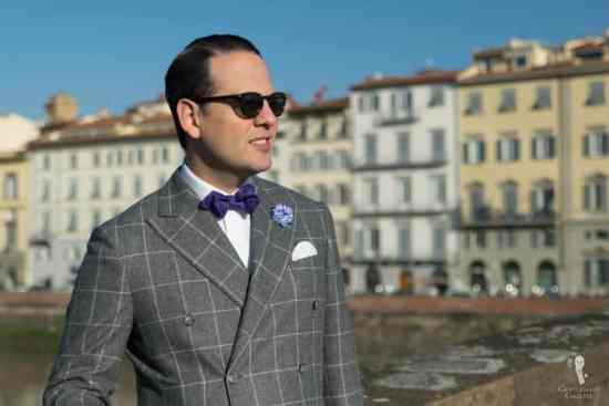 Sven Raphael Schneider wearing a DB flannel suit, purple paisley bow tie and cornflower boutonniere from Fort Belvedere