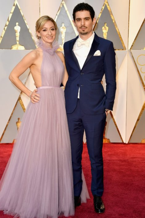 Damien Chazelle in striped blue tux with slim nothced lapels, white satin bow tie, wihtout cummerbund and black patent leather shoes