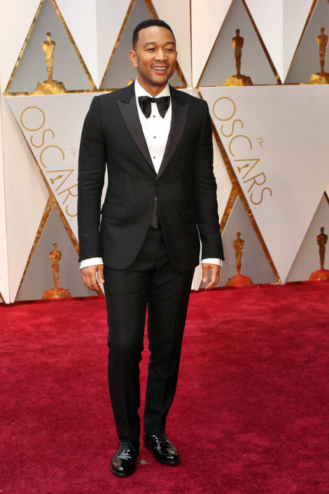 John Legend wearing a 70s inspired huge, floppy bow tie with peaked lapel 1 button tux with flap pockets and patent leather captoe Oxfords. Note, his sleeves are too long