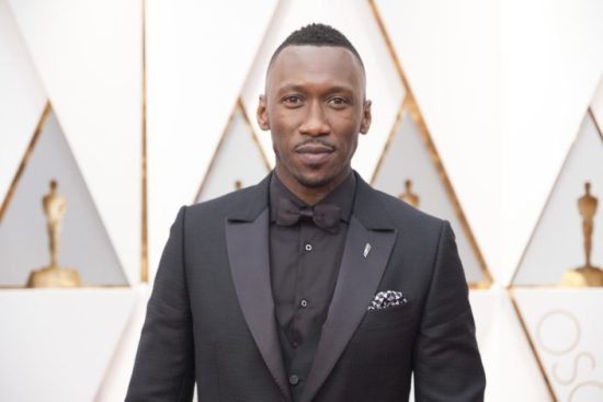 Mahershala Ali Oscar Winner for Best Supporting Role wearing a black shirt, and a day vest with his textured peaked lapel jacket and wide collar. A solid white shirt would have looked