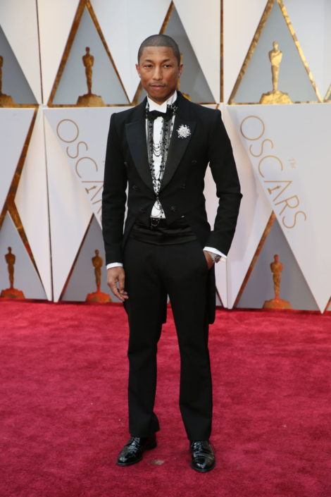 Pharrell Williams in a costume of tailcoat neckchains and huge wristwatch