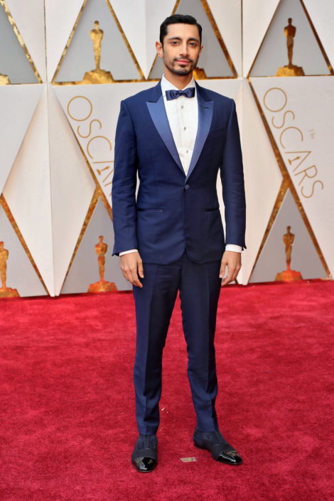 Riz Ahmed in navy blue tuxedo with navy satin bow tie and blue black suede shoes